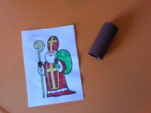 Choisir un dessin de St Nicolas et le faire colorier. Le coller sur un support cartonné et découper le contour. Prendre un rouleau de papier toilette, le peindre ou le customiser avec du papier crépon.